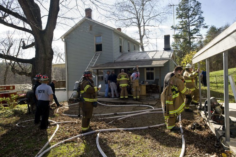 Firefighters stand outside this home at 1646 Star Tannery Road in Frederick County. The home was damaged by fire on Monday morning. Rich Cooley/Daily